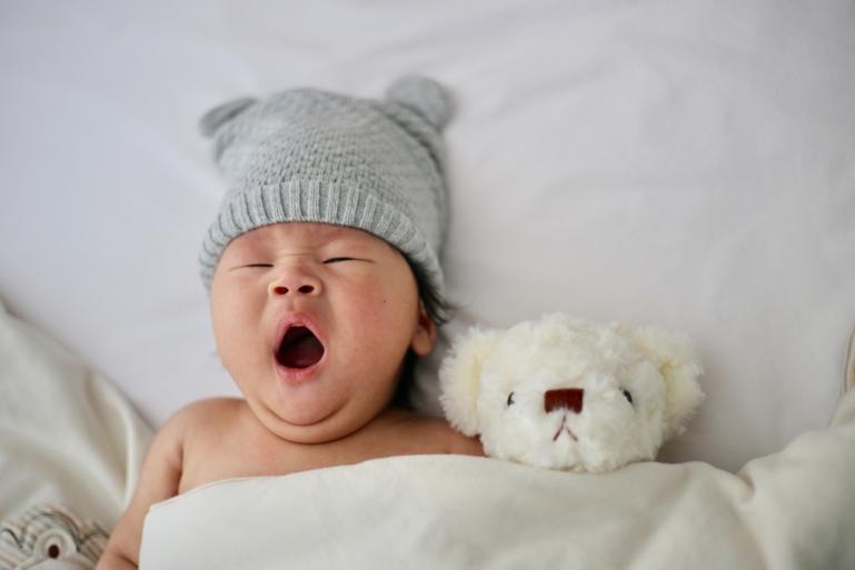Baby in bed aan het gapen